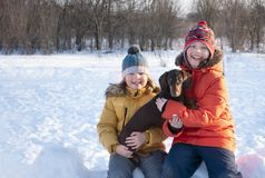 Happy boy playing with white dog in winter day, dog and child on stock photography