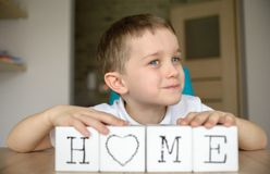 Happy boy plays with cubes and puts it together in word Royalty Free Stock Photo
