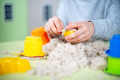 Happy boy plays kinetic sand at home stock photo