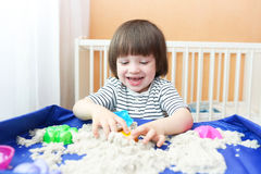 Happy boy plays kinetic sand at home Stock Image