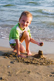 The happy boy plays sand royalty free stock photo