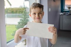 Happy boy in a polo shirt, holding an empty copyspace sheet of paper Royalty Free Stock Photography