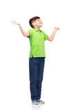 Happy boy in polo t-shirt raising hands up. Childhood, achievement, gladness and people concept - happy smiling boy in green polo t-shirt raising hands and stock photo