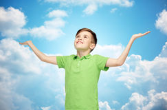 Happy boy in polo t-shirt raising hands up. Childhood, achievement, gladness and people concept - happy smiling boy in green polo t-shirt raising hands and royalty free stock image