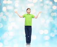 Happy boy in polo t-shirt raising hands up Stock Images