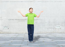 Happy boy in polo t-shirt raising hands up Royalty Free Stock Photography