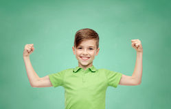 Happy boy in polo t-shirt showing strong fists. Childhood, education, power, strength and people concept - happy smiling boy in green polo t-shirt showing strong royalty free stock image