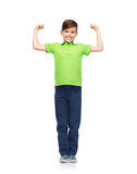Happy boy in polo t-shirt showing strong fists Royalty Free Stock Photos