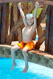 Happy boy by pool. Happy young boy with face mask and arms in air sat on wooden bridge over swimming pool Stock Photography