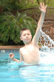 Happy boy in pool. A view of a young boy as he splashes water and plays happily in the cool water of a swimming pool on a hot summer day royalty free stock image