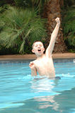 Happy boy in pool. A view of a happy boy with his arm raised high as he jumps and plays in the refreshing water of a swimming pool on a summer day stock image