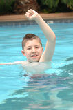 Happy boy in pool. A close up view of a young boy standing in water up to his neck happily playing in a swimming pool on a hot summer day stock images