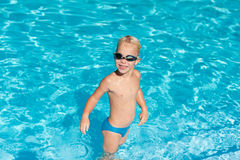 Happy boy in pool. Cheerful boy splashing in the water stock image
