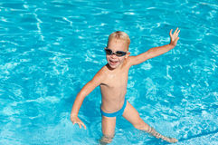Happy boy in pool. Cheerful boy splashing in the water royalty free stock photos