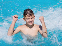 Happy boy in pool. Happy teen boy jumping in the swimming pool at aquapark. Cute child having fun enjoyable time on vacation. He laughing and splashing water Stock Images