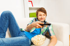 Happy boy with popcorn relaxing on white sofa Stock Photos