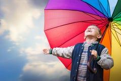 Happy boy portrait with bright rainbow umbrella Stock Image