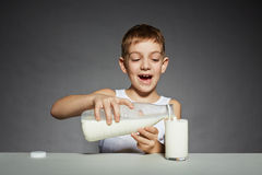 Happy boy pouring milk into glass Royalty Free Stock Photo