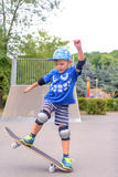Happy boy practicing balancing on a skateboard Stock Images