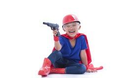 Happy boy pretending to be a superhero with toy gun Royalty Free Stock Photos