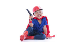 Happy boy pretending to be a superhero with toy gun. On white background Stock Image