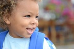 Happy boy profile. Biracial curly boy looking to side smiling. having a backack Royalty Free Stock Photo