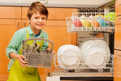 Happy boy pulling out cutlery of the dishwasher. Portrait of happy kid boy pulling out a basket with clean cutlery of the dishwasher in the kitchen stock photos