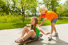 Happy boy pushes smiling girl with closed eyes. Sitting on skateboard with arms apart Royalty Free Stock Images