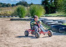 Happy boy races around a dirt track stock photos