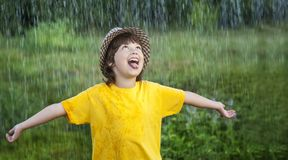 Happy boy in rain summer outdoors.  royalty free stock photography