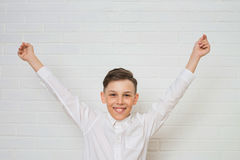 Happy boy with raised hands up celebrating victory. Royalty Free Stock Image