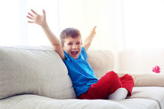 Happy boy raising hands while sitting on sofa Stock Image