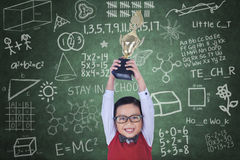 Happy boy raising trophy in class royalty free stock image