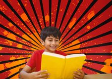 Happy boy reading against red, black and orange splattered background. Digital composite of Happy boy reading against red, black and orange splattered background Royalty Free Stock Images