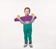 Happy boy received a gift brand new skate board. Cute little guy in green trendy pants posing with his skateboard against a white background. Happy boy received Stock Images