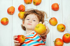 Happy boy with red apples on light wooden floor. Top view. Royalty Free Stock Image
