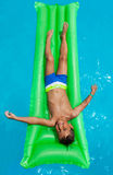 Happy boy relaxing on green inflatable mattress Stock Photo