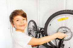 Happy boy repairing his bicycle wheel with spanner Stock Photos