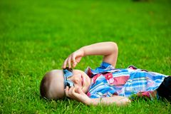 Happy boy resting lying on green grass Stock Image
