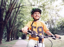 Happy boy ride a bicycle in city park Stock Photos