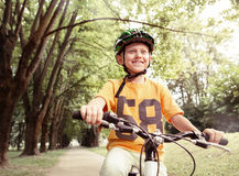 Happy boy ride a bicycle in city park Stock Images