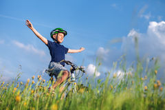 Happy boy ride a bicycle without hands and enjoy with sunlight Stock Photography