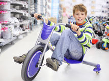 Happy boy rides blue tricycle and looks Royalty Free Stock Image