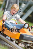 Happy boy riding at bobsled coaster rail trac. Happy boy riding at bobsled roller coaster rail track in summer amusement park royalty free stock photography