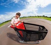 Happy boy riding empty supermarket shopping cart Royalty Free Stock Image