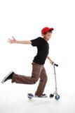 Happy boy riding a scooter Stock Photos