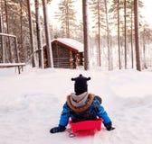 Happy boy riding sledge in snowy winter Stock Photos