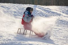 Happy boy riding at the slide on snowy hill royalty free stock photo