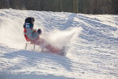 Happy boy riding at the slide on snowy hill stock photos