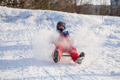 Happy boy riding at the slide on snowy hill royalty free stock photography